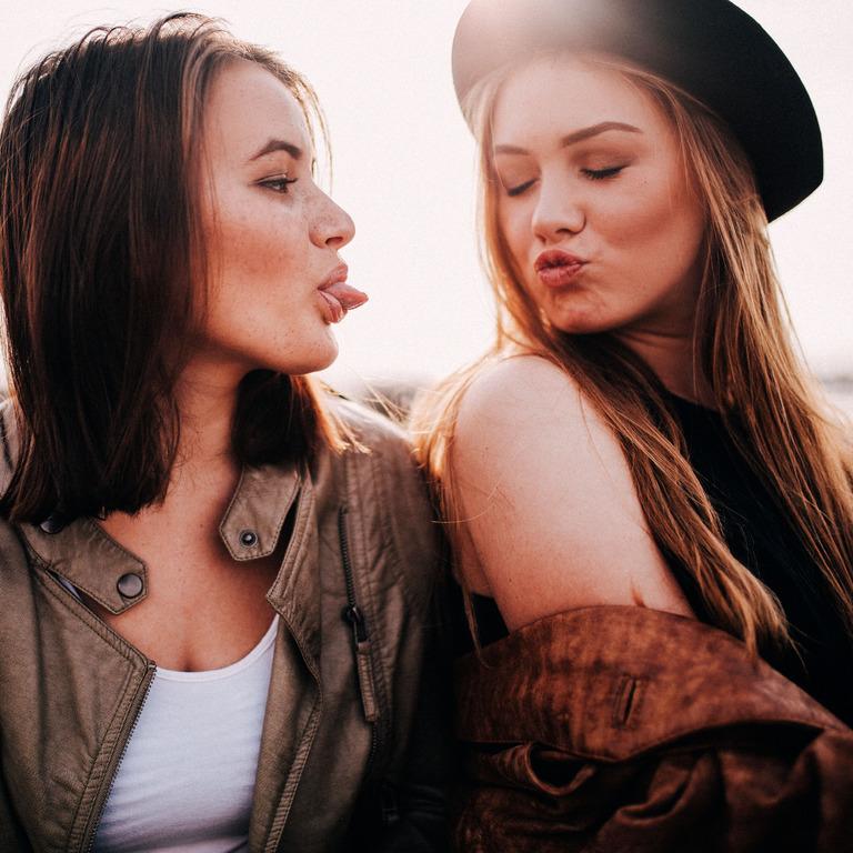 eine Teenagerin macht einen Kussmund in Richtung ihrer Freundin, die Freundin streckt ihr die Zunge raus