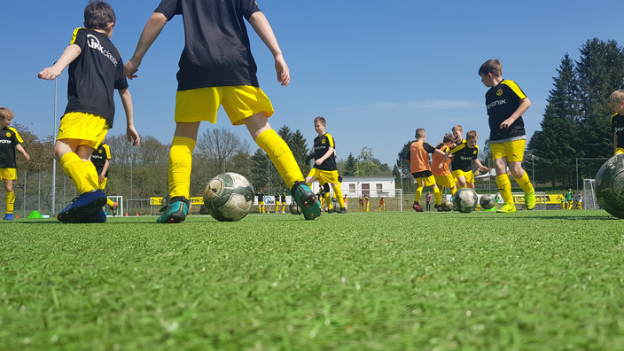 eine Gruppe Zehnjähriger in BVB-Trikots beim Technik-Training auf dem Fußballplatz