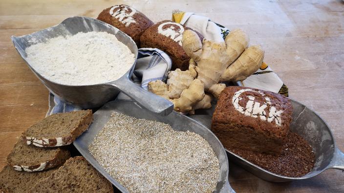 Zutaten und fertige Laibe des IKK-Brotes schön dekoriert auf einem Holztisch