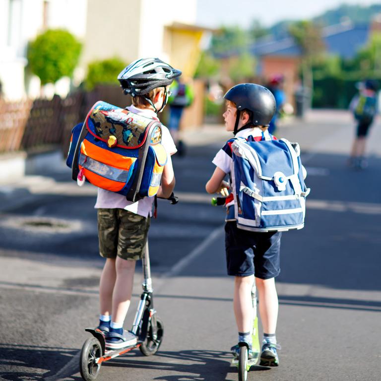 Zwei Jungen mit Ranzen und Tretroller auf dem Weg zur Schule
