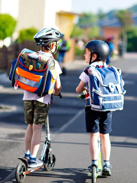 Zwei Grundschüler mit Schulranzen auf dem Rücken fahren mit dem Tretroller zur Schule