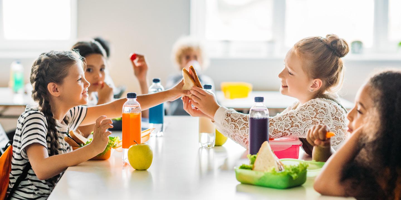 Schulkinder sitzen in der Pause an einem Tisch und essen Brote