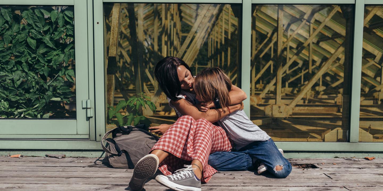 Mutter und Kind sitzen auf Holzterrasse und umarmen sich.