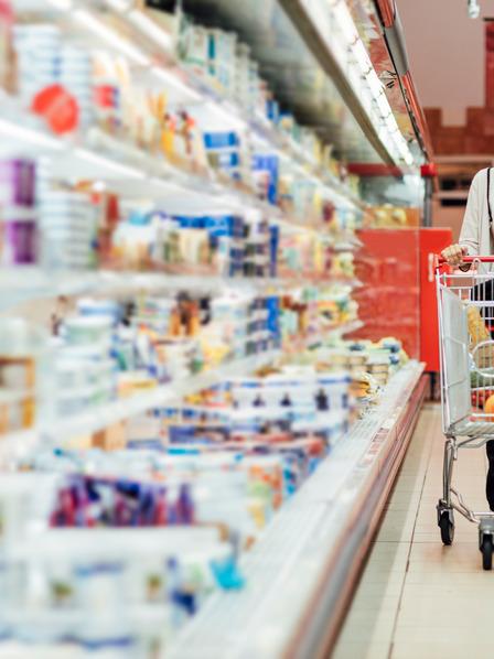 Frau fährt mit einem Einkaufswagen an einem Supermarktregal entlang