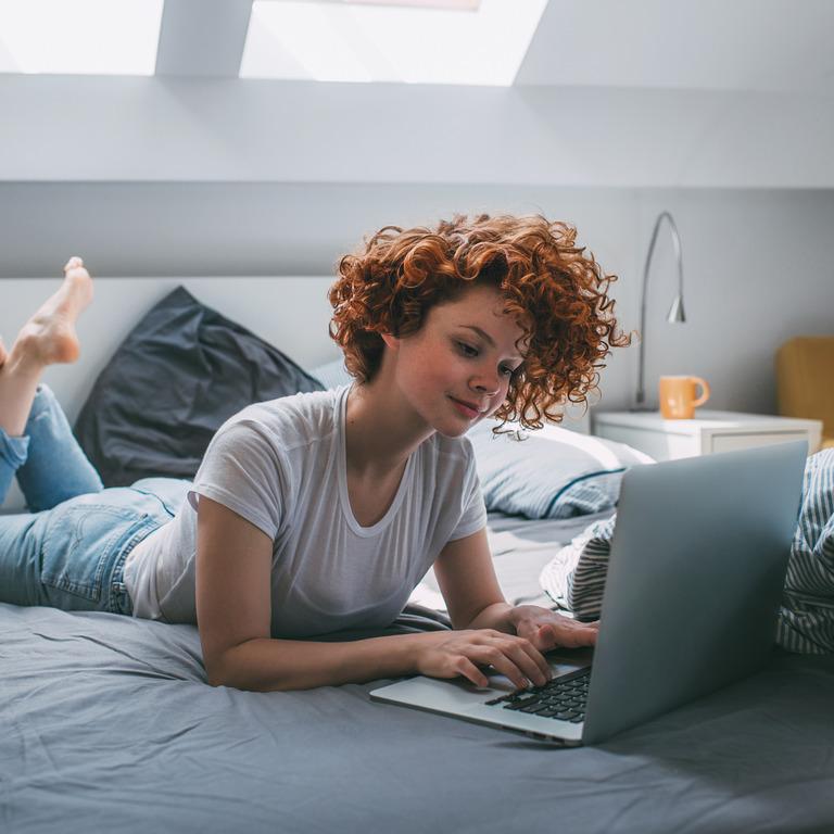 junge Frau liegt mit ihrem Laptop auf dem Bett und recherchiert