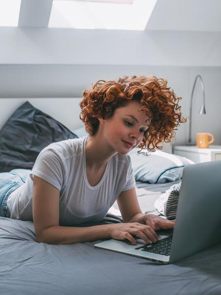 junge Frau liegt auf ihrem Bett und benutzt ihren Laptop