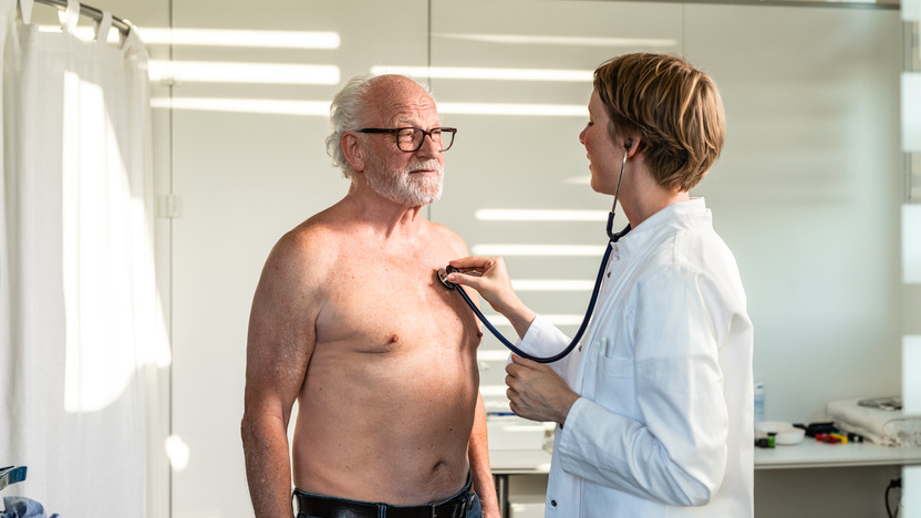 Ärztin horcht die Lunge eines älteren Patienten ab