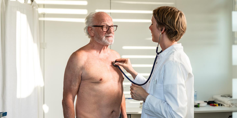 Ärztin hört mit Stethoskop das Herz eines grauhaarigen Mannes ab.