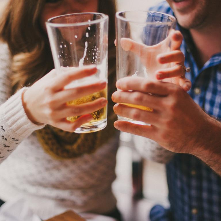 Paar stößt mit zwei Gläsern Bier an