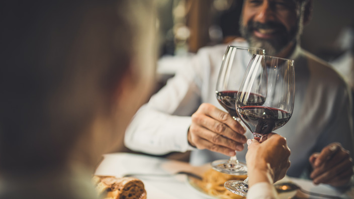 Paar stößt während des Abendessens in einem Restaurant mit einem Glas Rotwein an