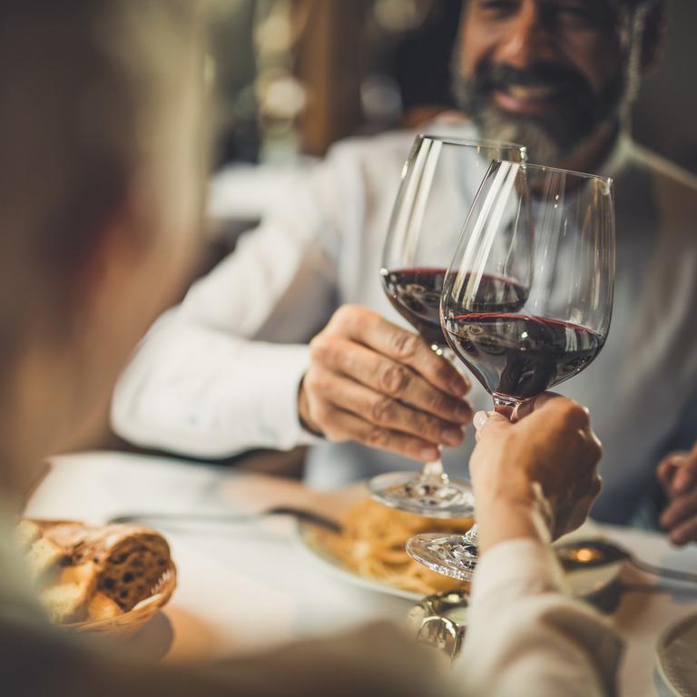 Paar stößt mit Rotwein an