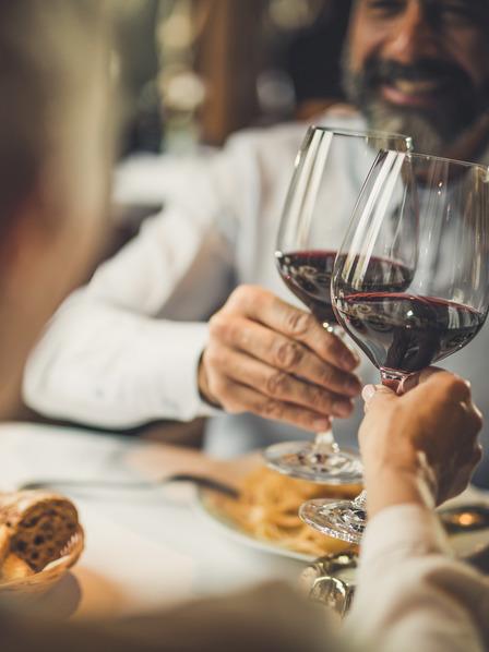 Paar stößt beim Restaurantbesuch mit zwei Gläsern Rotwein an