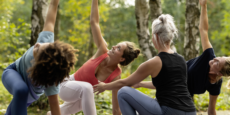 Frauen mit Trainerin beim Yoga-Kurs