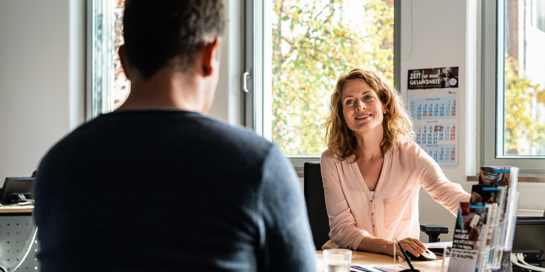 Kundenberaterin berät IKK-Versicherten in einem Service-Center