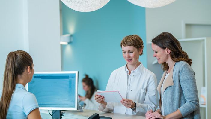 Patientin mit Ärztin und Sprechstundenhilfe am Empfang einer Arztpraxis