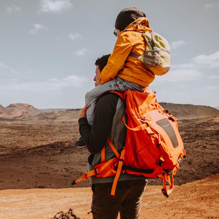 Vater trägt seinen Sohn auf den Schultern und beide schauen über eine Wüstenlandschaft