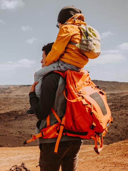 Vater im Trekking-Outfit trägt seinen Sohn auf den Schultern und blickt in eine Wüstenlandschaft