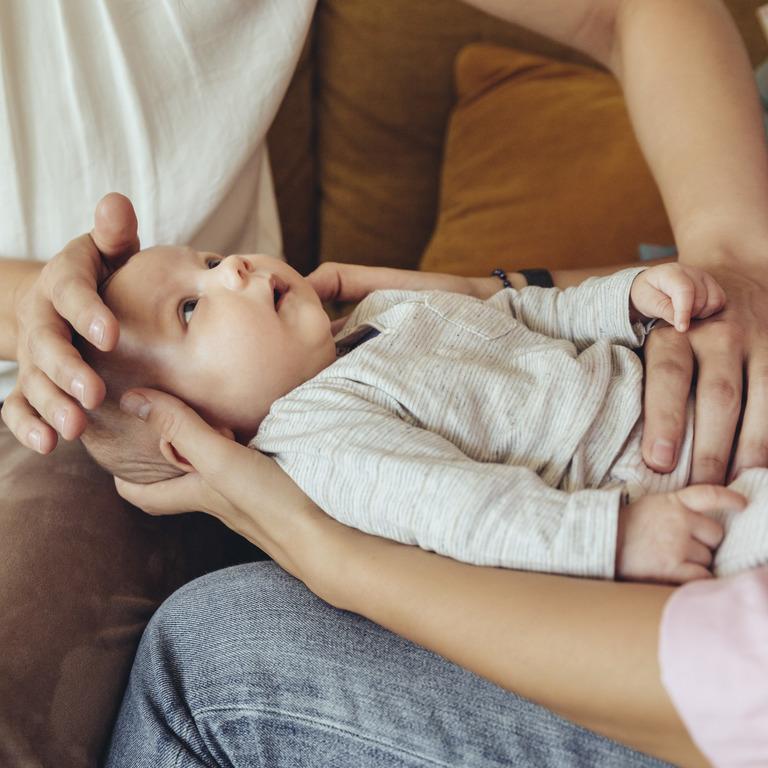Mutter hält ihr Baby in Rückenlage auf dem Schoß während die Hebamme es untersucht