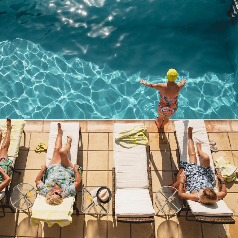 vier ältere Damen an einem Swimmingpool