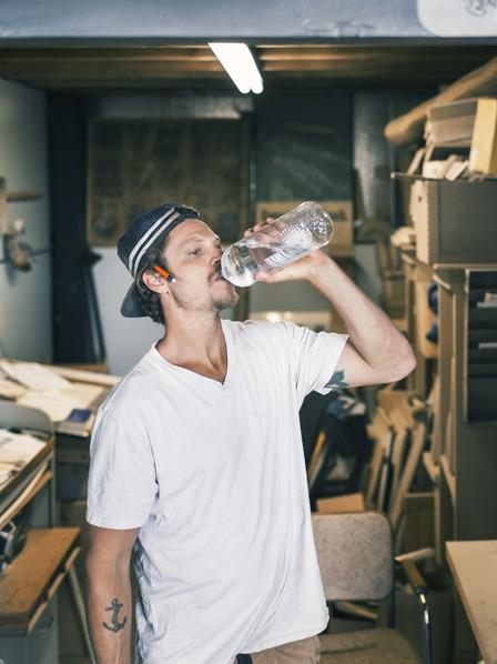 verschwitzter Handwerker trinkt Wasser