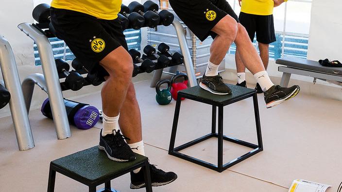 Zwei Spieler des BVB Dortmund machen Kniebeugen auf einem Hocker im Fitnessstudio