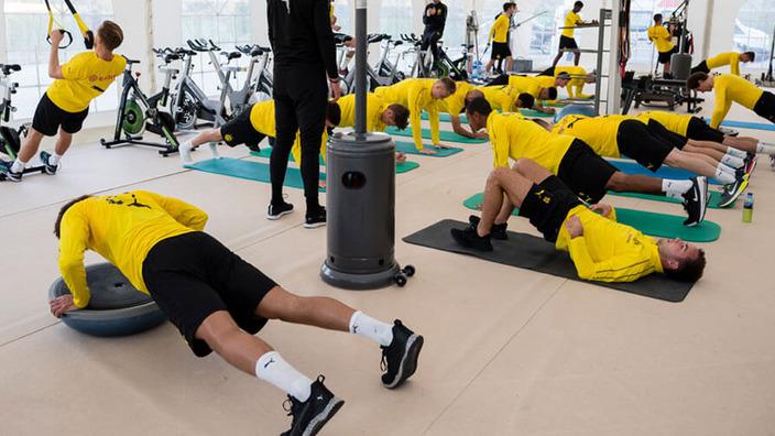 Fußballmannschaft BVB Dortmund trainiert im Fitnessstudio an unterschiedlichen Sportgeräten