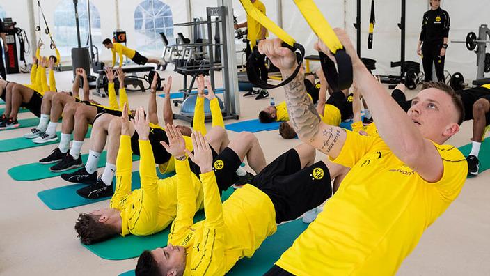 Spieler des BVB Dortmund trainieren im Fitnessstudio an unterschiedlichen Sportgeräten