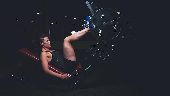 Junge Frau in Sportkleidung trainiert mit der Beinpresse