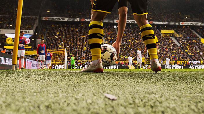 Beine eines BVB-Spielers, der den Ball für den Eckstoß ablegt