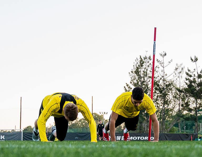 BVB-Spieler machen Liegestütze auf dem Rasen