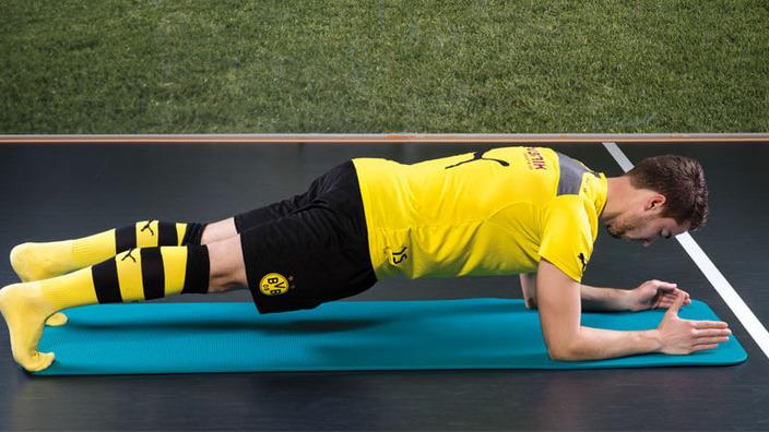 BVB-Spieler macht einen Unterarmstütz auf einer Sportmatte