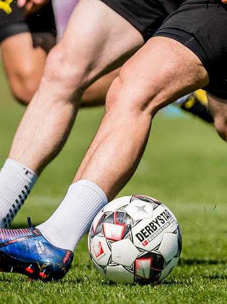 Beine von Fußballspielern, die um den Ball kämpfen