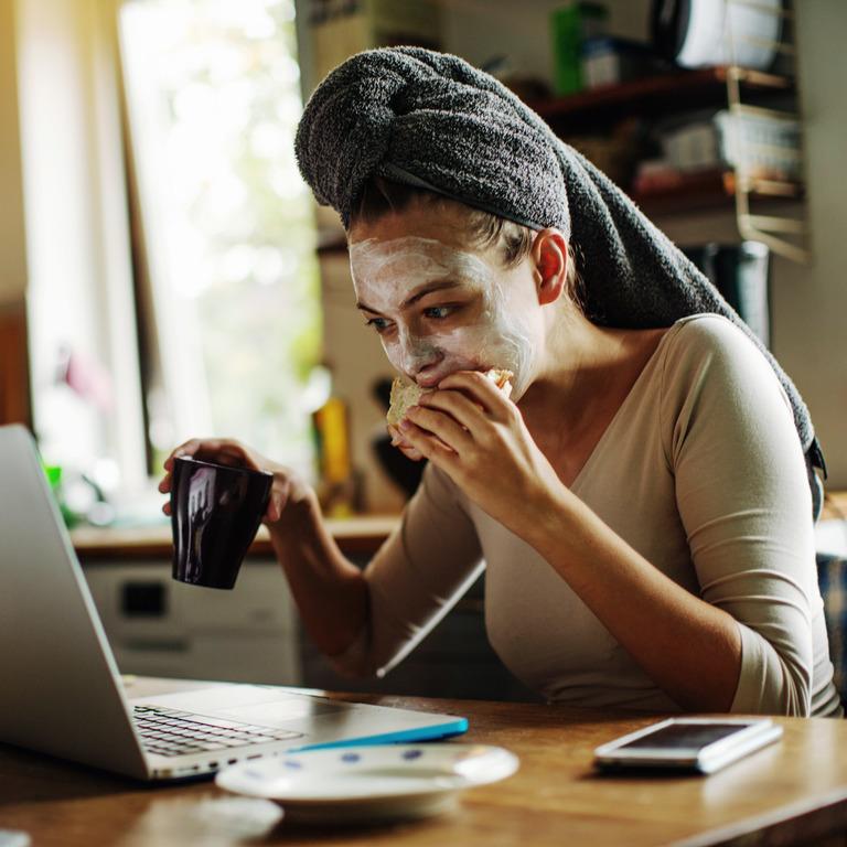 Junge Frau mit Handtuchturban und Gesichtsmaske isst ein Brot vor dem Laptop