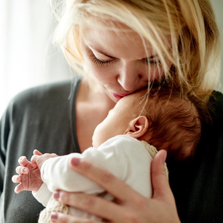 Mutter hält ihr Baby auf dem Arm und küsst es auf die Stirn