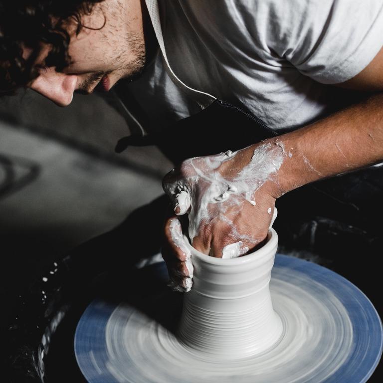 Mann formt am Tonvase an Maschine.