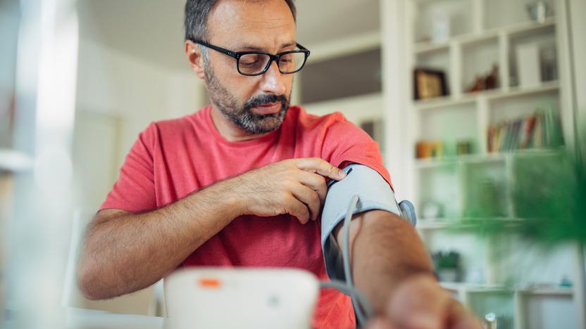 Mann misst den Blutdruck mithilfe eines Messgeräts