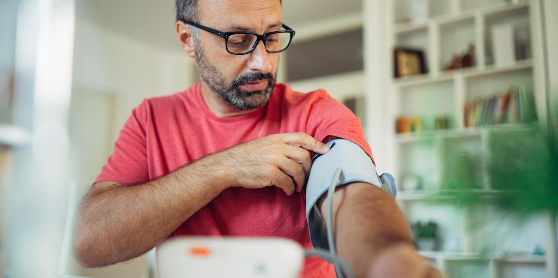Mann mittleren Alters mit Brille misst Blutdruck am Arm.