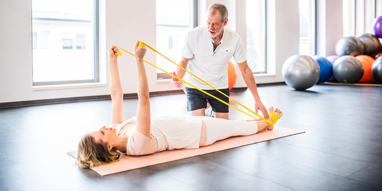 Physiotherapeut in Rehaklinik zeigt Patientin Übungen mit einem Thera-Band.