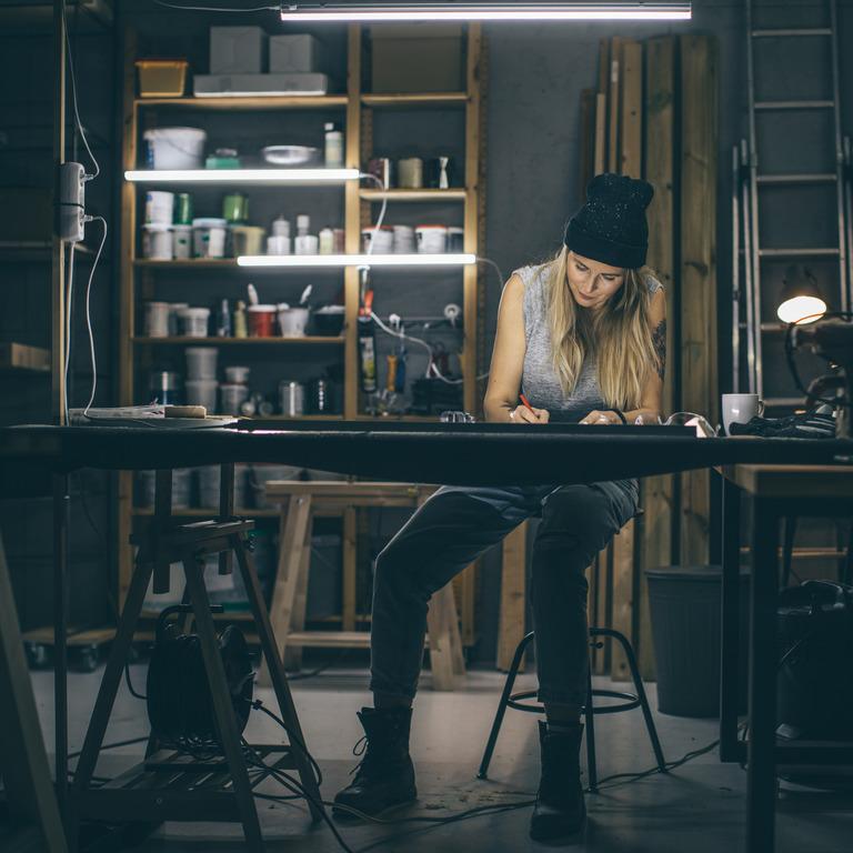 Handwerkerin sitzt spätabends an ihrem Schreibtisch