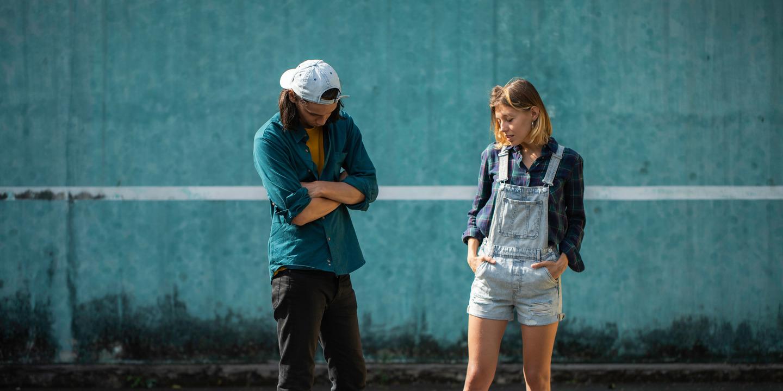 Deutliche Körpersprache: Mann mit verschränkten Armen und Frau mit Händen in der Tasche schauen zu Boden