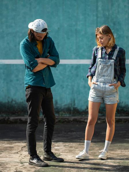 junger Mann verschränkt die Arme vor dem Körper und schaut auf den Boden, junge Frau hat die Hände in den Hosentaschen und schaut ebenfalls nach unten