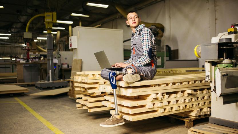 Junger Mann mit Beinprothese sitzt im Schneidersitz auf einem Holzhaufen mit dem Laptop auf dem Schoß