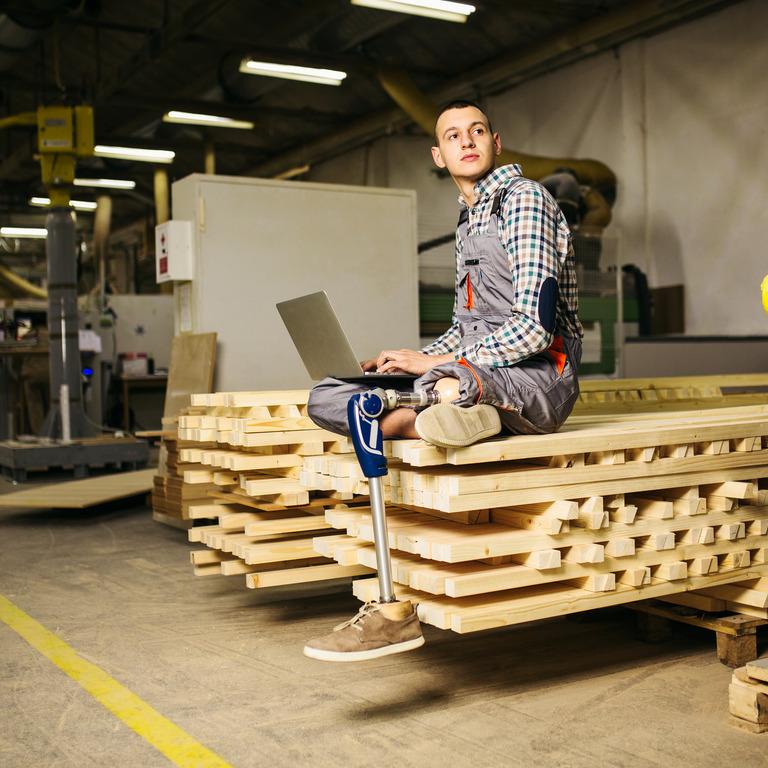 junger Tischler mit einer Beinprothese sitzt mit einem Laptop auf einem Stapel Holzleisten