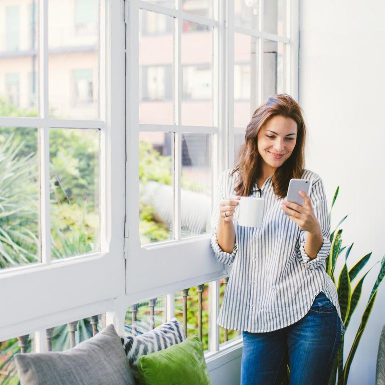 Frau steht am Fenster, trinkt Kaffee und checkt ihr Smartphone