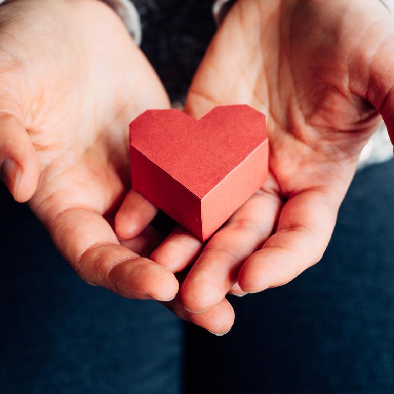 Zwei Hände, die ein rotes Herz aus Holz halten