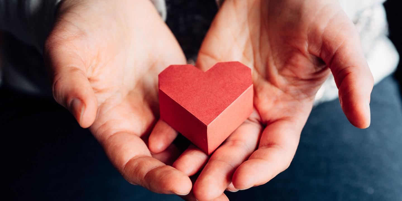 Hände halten ein rotes Papierherz fest.