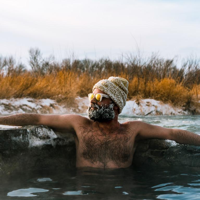 Mann sitzt in heißer Quelle, sein Bart, die Wollmütze und das Gestell seiner Sonnenbrille sind weiß vor Frost.