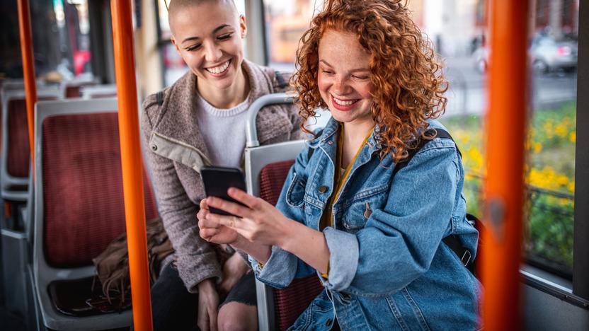 Zwei junge Frauen sitzen im Bus und schauen lachend auf ein Smartphone