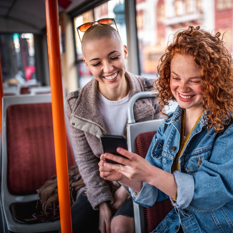 Zwei junge Frau sitzen in der Straßenbahn hintereinander, eine Frau zeigt etwas auf ihrem Smartphone