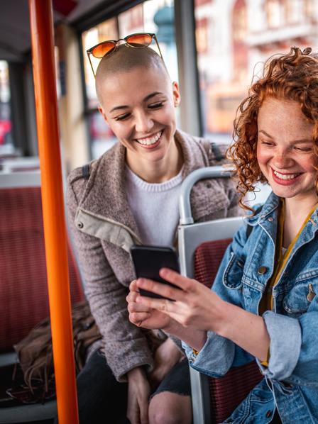 Zwei junge Frauen sitzen im Bus und schauen lachend auf ein Smartphone.